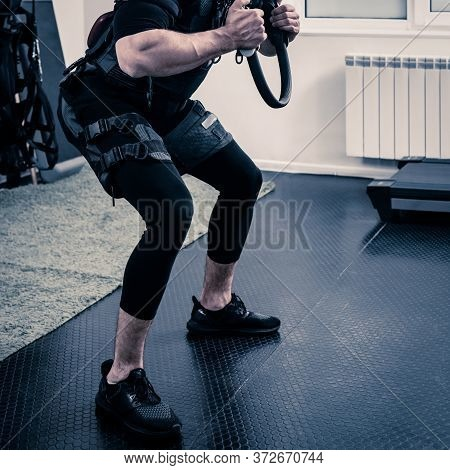 Man In Electrical Muscular Stimulation Suit Doing Squat With Resistance Ring