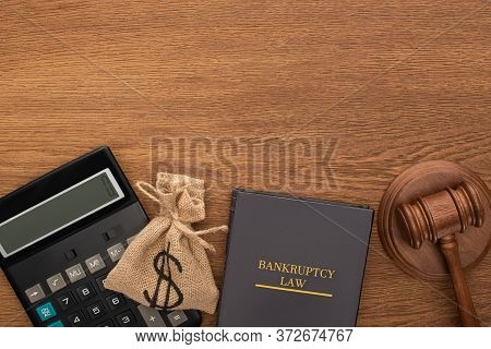 Top View Of Bankruptcy Law Book, Money Bag, Calculator And Gavel On Wooden Background