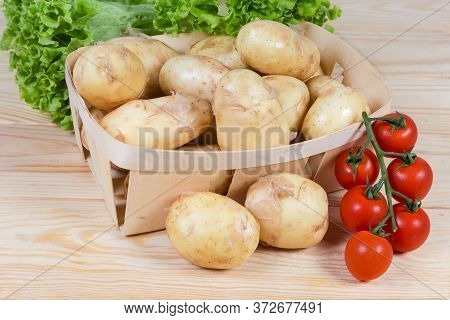 Raw Washed Yellow Young Potatoes With Unpeeled Thin Skin In The Small Wooden Basket And Beside, Lett