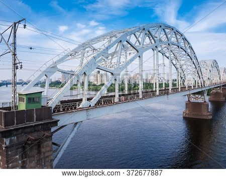 Three Spans Of The Railroad Bridge With Steel Riveted Arch Trusses Over The River. Fragment Of The D