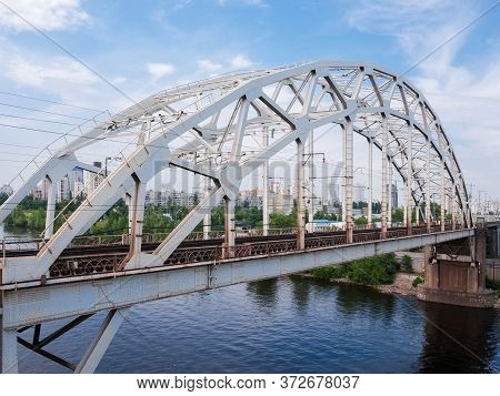Span Of The Railroad Bridge With Steel Riveted Arch Truss Over The River Against The City Buildings
