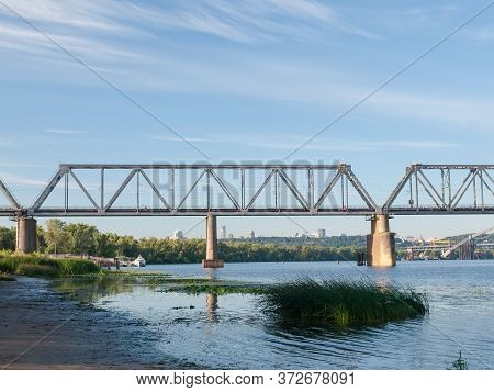 Left-bank Part Of The Railroad Bridge Made Of Steel Trusses And Stone Supports Across River. Podilsk