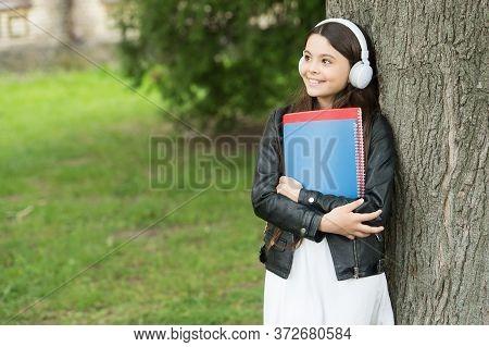 Listening Lessons. Happy Girl Practice Listening Skills Outdoors. Little Child Enjoy Listening To Mu