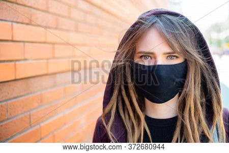 Portrait Of A Girl With Dreadlocks With A Medical Mask On Her Face That Protects Against Coronovirus
