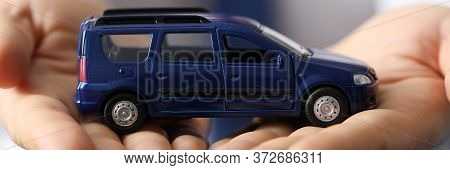 Closeup, Man In Shirt Holds Blue Toy Minivan Car. Favorable Car Insurance. Inspection And Diagnostic