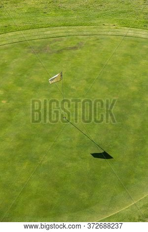 Aerial View Of A Golf Course. In Detail You Can See The Lawn Of The Hole And White Flag Of Signaling