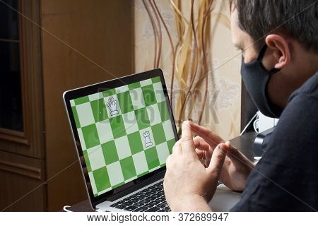 A Man In A Medical Mask Solves A Chess Problem Online. Chess Board With Figures On A Laptop Screen.