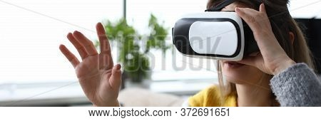 Girl Sitting Home Looking Through Virtual Glasses. Virtual Reality Simulates Exposure And Response T