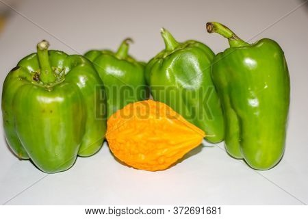 Yellow Bitter Gourd Between Green Capsicum With Isolated Background, Odd One Out