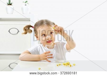 A Child Looks At A Capsule With Fish Oil, Tastes Omega3, A Glass Of Water In His Hand And A Capsule,