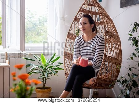 Beautiful Woman Relaxing At Home In Swing Chair. Woman Relaxing In Swing Chair At Home. Hipster Life