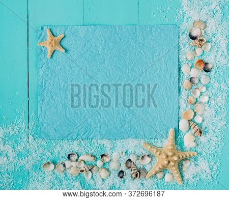 Crumpled Sheet Of Paper On Wooden Turquoise Background. Sea Shells Around. Place For Text, Banner Te