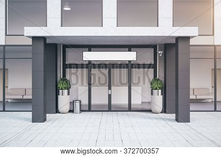 Front View Of Entrance Of Contemporary Office Building With Plants. Business Corporate And Company C