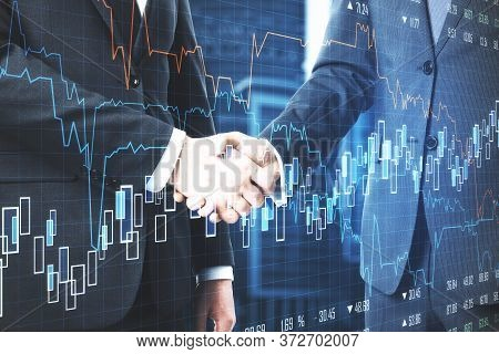 Business People Shaking Hands With Creative Stock Chart On Blurry City Backround. Teamwork And Deal