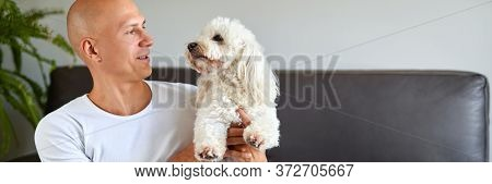 Handsome Man With Cute White Dog At Home On Sofa