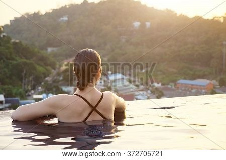 Brunette Looks At Green Forestry Hills Sitting In Hotel Swimming Pool Water With Bright Sunlight Ref