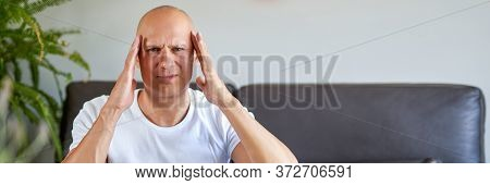 Feeling Depressed. Desperate Man Keeping His Hand On Forehead While Sitting On The Couch At Home.