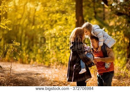 Family With Children Walking In Autumn Park. Walks In Nature. Beautiful Yellow And Orange Trees.