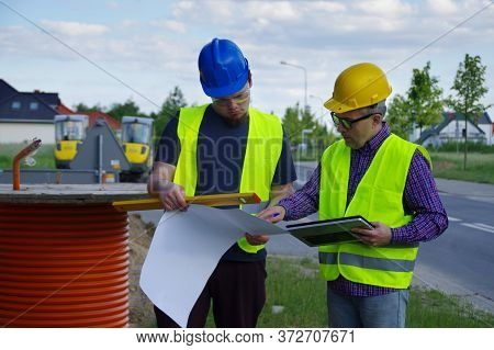 Teamwork Planning And Implementation. Engineer And Worker In Helmets On A Construction Site. A Busin