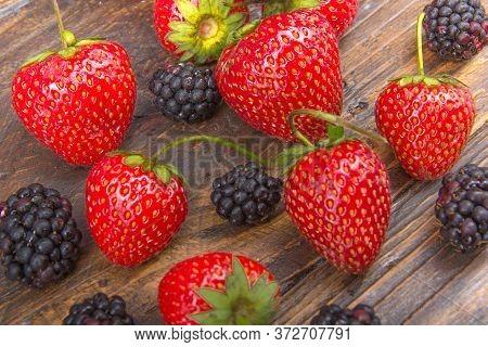Blackberries, Strawberrieson Wooden Table Background, Spilled From A Jar. Antioxidants, Detox Diet,