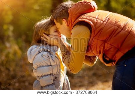 Dad Plays And Hugs With Daughter In Autumn Park. Nature Walks. Paternity.
