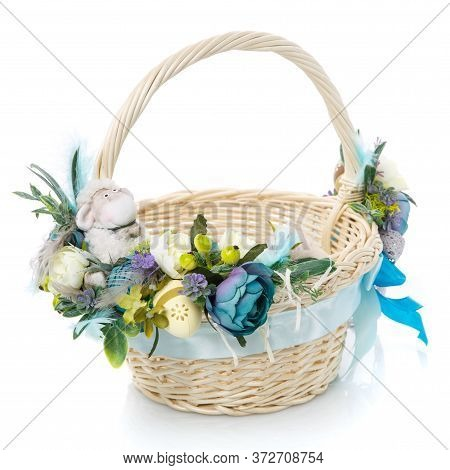 Easter Basket On White Background. Decorated With Flowers In Blue And A Small Decorative Sheep. Ribb