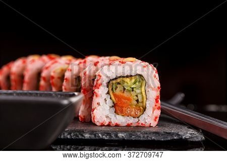 Japanese Sushi With Soy Sauce And Chopsticks On Black Background.
