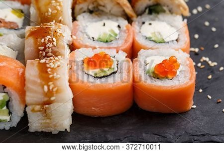 Two Types Of Sushi With Salmon And Tuna, Avocado And Cucumber, Cheese, Sesame And Caviar On A Black