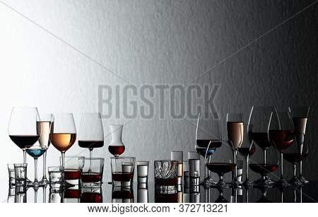 Set Of Various Alcoholic Beverages In Glasses On A Black Reflective Background. In The Presence Of L