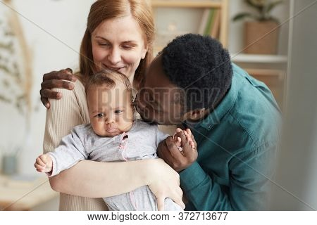 Waist Up Portrait Of Loving Interracial Family At Home, Focus On African-american Man Kissing Cute M