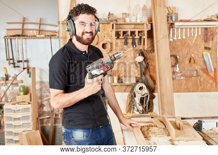 Young man as a joiner. Trainee with a hand drill in the workshop