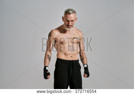 Half Naked Middle Aged Athletic Man, Kickboxer Looking Angry, Agressive, Standing In Studio Over Gre