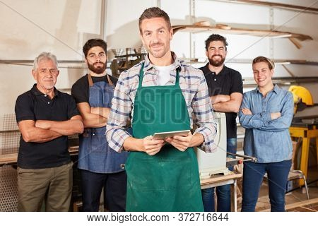 Young man as a craftsman trainee in front of carpenter colleague in joinery workshop