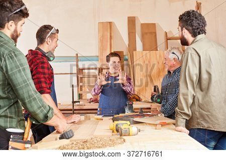 Artisan team and young apprentice woman in teaching together at the workbench