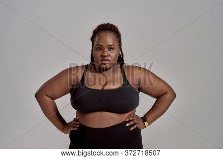 Plump, Plus Size African American Woman In Black Sportswear Looking At Camera While Standing In Stud