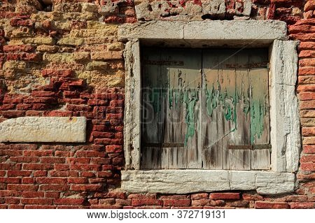 Old Decrepit Shuttered Window In A Crumbling Brick Wall