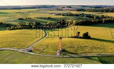 Landscape With Fields During Sunset And Yellow Metal Lookout Tower In The Foreground, Aerial Photo,