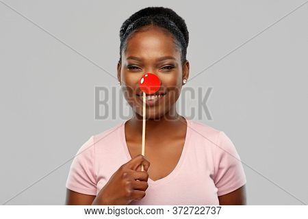 red nose day, party props and photo booth concept concept - happy african american young woman with clown nose over grey background