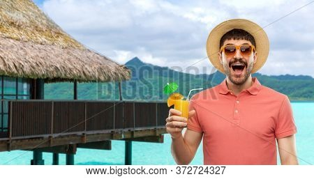 summer holidays, vacation and travel concept - happy smiling young man in sunglasses and straw hat with orange juice cocktail over bungalow on tropical beach background in french polynesia