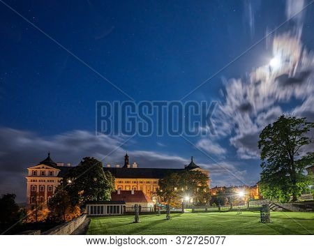 City Park In Front Of A Monastery At Night With Stars And Clouds, Broumov, Czech Republic.