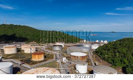 Aerial View Of A Lot Of Oil Depot Gas Storage Tank Near Sea On Blue Sky Back Ground.