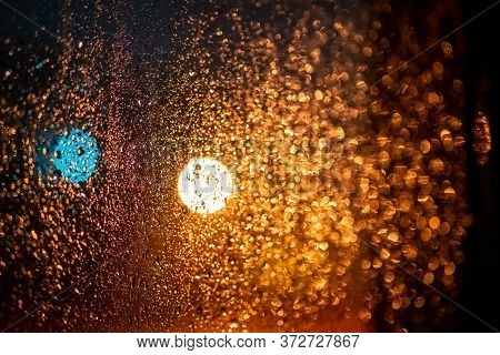 Raindrops On A Window With The City Lights At Night, Abstract Blurred Background With Colored Lights