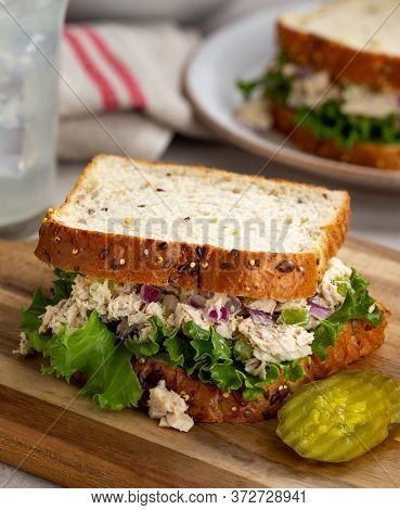 Tuna Fish Salad And Lettuce Sandwich On Multiseed Bread With Sliced Pickles On A Wooden Cutting Boar