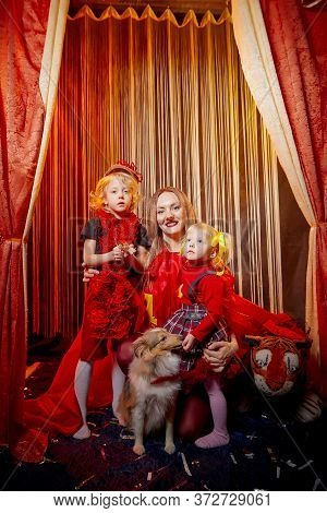 Family With Dog During Stylized Theatrical Circus Photo Shoot In Beautiful Red Location. Model Mothe