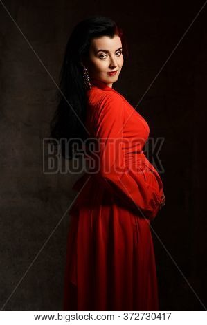 Noble Pregnant Brunette Woman In Red Elegant Maxi Dress Stands Side To Us Embracing Belly, Looking A