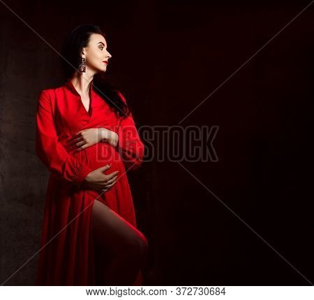 Young Tall Sensual Pregnant Woman In Red Elegant Maxi Dress Embraces Belly And Looking Aside At Copy