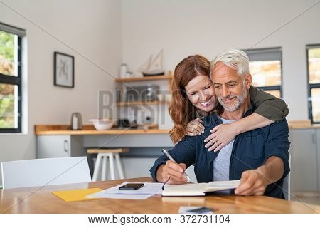 Loving mature wife embracing husband from behind while writing in book. Happy middle aged couple making to do list of purchases and discussing future plans, copy space. Senior man working at home.
