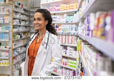 Portrait of african american pharmacist working at pharmacy wearing labcoat with stethoscope. Cheerful young mixed race pharmacist woman in pharmacy drugstore smiling. Young multiethnic chemist owner.