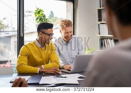 Smiling business men discuss project during meeting. Happy apprentice showing report on laptop to his boss in modern office. Multiethnic colleagues discussing during brainstorming.