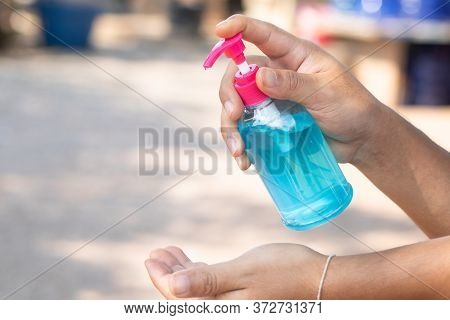Hand Sanitizer, Alcohol Bottle, Held In Hand. Disinfecting Concept: Liquid Soap, Squeezing Blue Gel